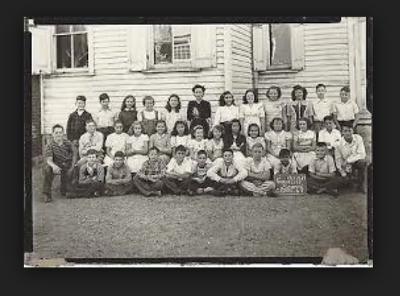 Pictured is a low resolution 1947 photo of students posing for a photo at the front side of the school. Image via Google Search.