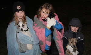 "Holding their pets after the fire are Haily with ""Chuck"", Mya with ""Storm"", and Bowe with Chuck."