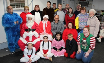 Volunteers pause for a quick photo with Mr. and Mrs. Claus.