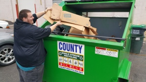 Pictured is Frank Latham placing flattened cardboard in the dumpster.